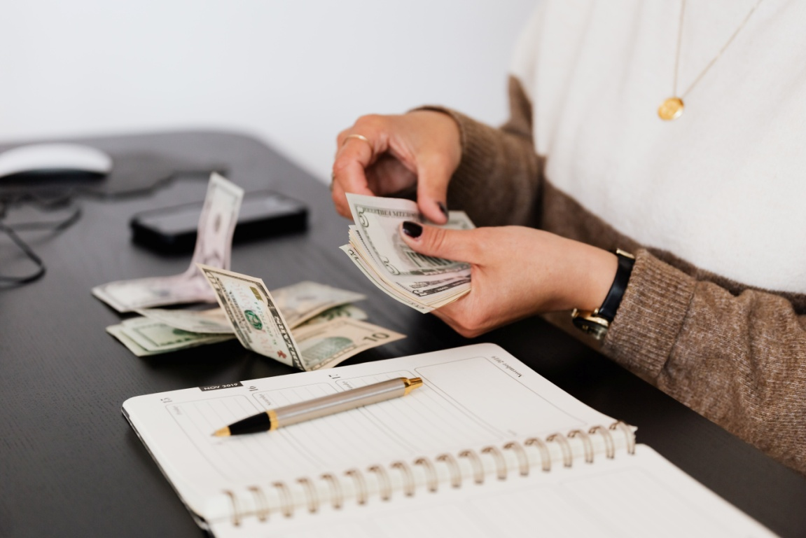 Payroll clerk counting money while sitting on the table