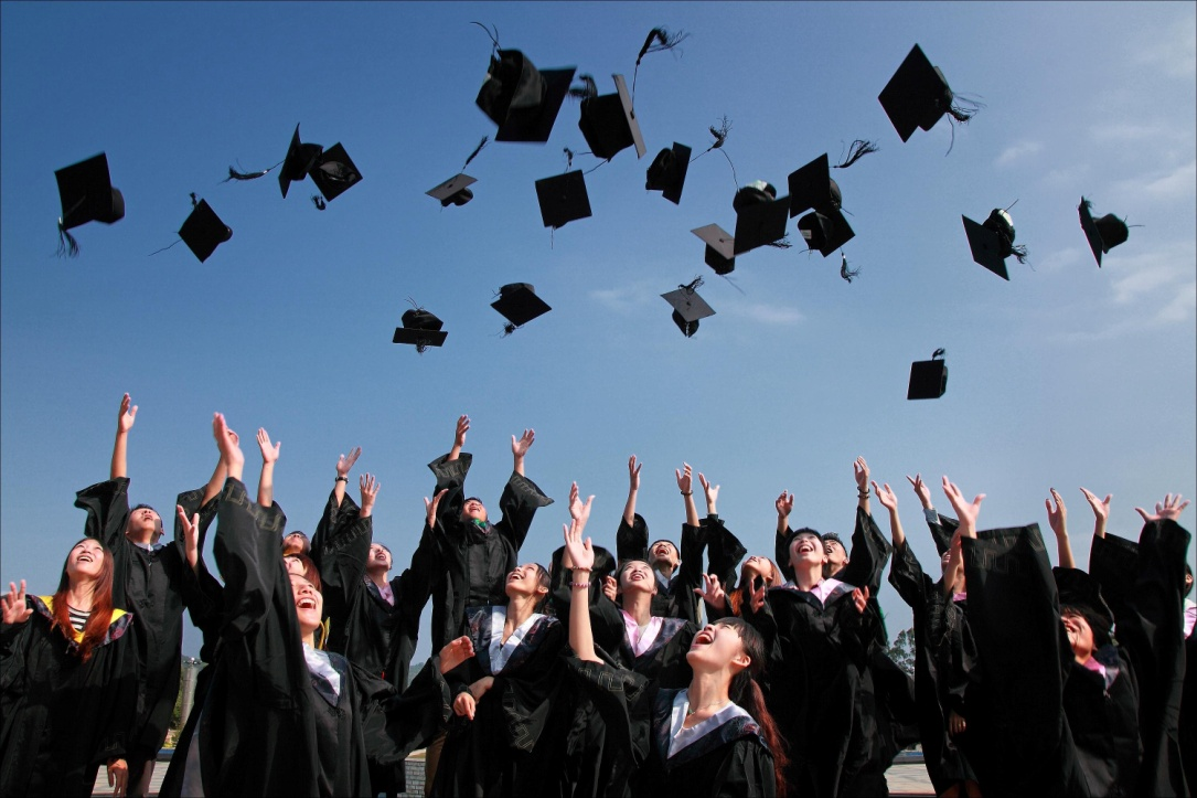 Newly graduated people wearing academy gowns throwing hats in the air