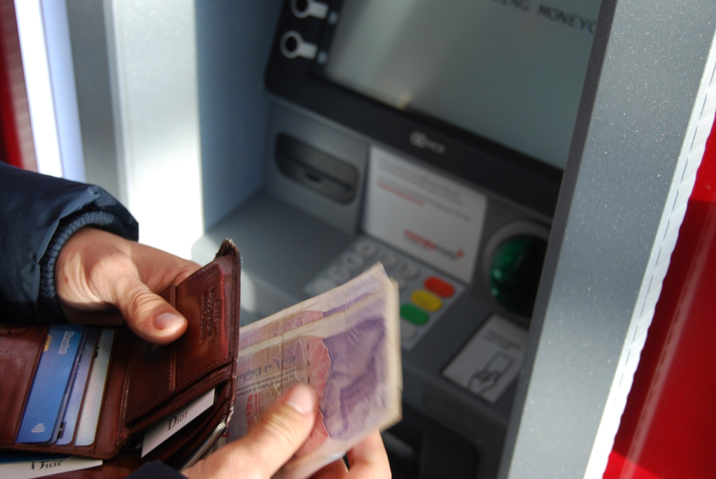 A person depositing money into their account using an ATM