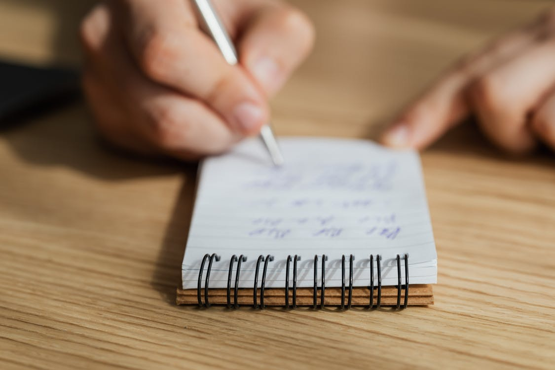 Crop man writing in notebook with pen