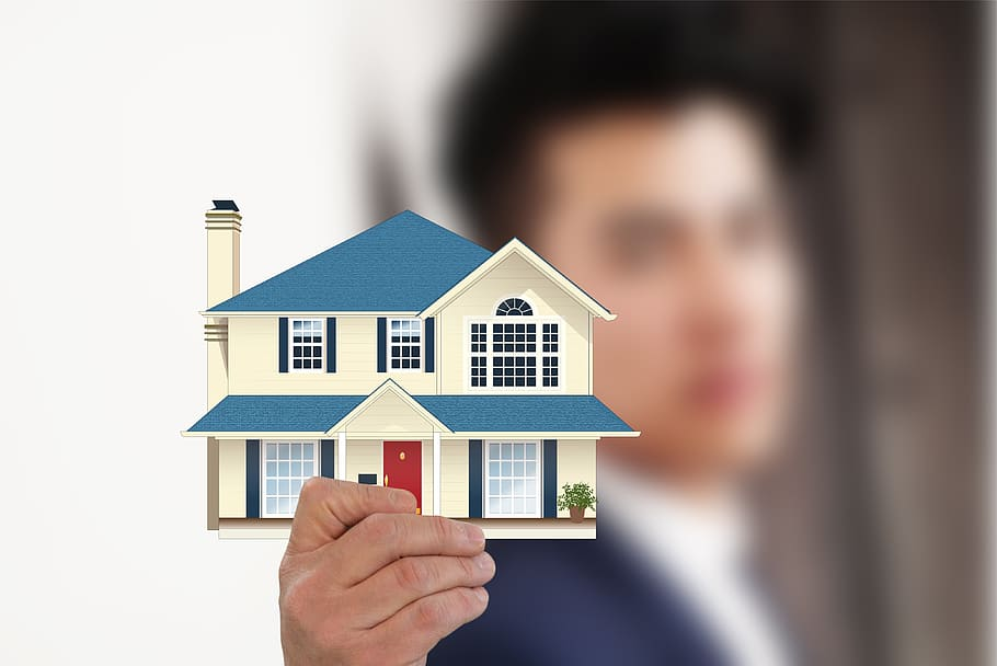 A real estate agent holding a cutout of a 2-story house