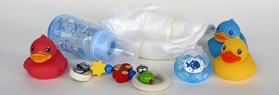 Baby supplies such as a diaper, rubber ducks, nipples, and toys placed on a surface.